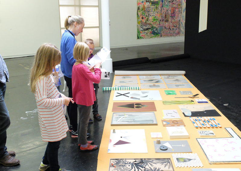 Some kids and me looking at several collages on the floor of the gallery.