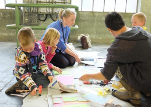 Artist, kids and me sitting on the floor, cutting colored paper.