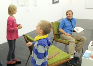 three kids talking with an artist in a chair.